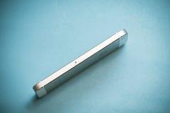 在蓝纸背景的金苹果计算机iPhone 5s 库存图片