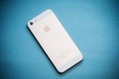 在蓝纸背景的金苹果计算机iPhone 5s 免版税库存照片