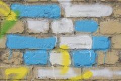 在蓝色、黄色和白色的几块被绘的砖在老肮脏的墙壁上,作为街道画 墙壁五颜六色的难看的东西纹理  免版税库存照片