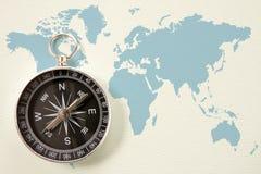 在蓝色世界地图的黑色指南针 库存照片