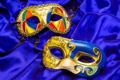 在蓝色丝绸的两个五颜六色的狂欢节面具 免版税图库摄影