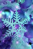 在蓝色光的点灯闪烁雪花和闪烁球形的圣诞节装饰品 免版税库存照片