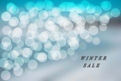 在蓝色冬天销售的蓝色和白色bokeh背景 库存照片