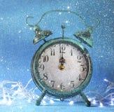在蓝色冰bokeh背景的葡萄酒时钟 概念新年度 减速火箭过滤与闪烁覆盖物 选择聚焦 库存照片