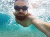 在蓝色净水的年轻人潜水 免版税库存照片