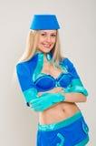 在蓝色制服打扮的迷人的空中小姐 免版税库存图片