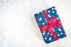 在蓝色包裹的礼物盒加点了与红色丝带的纸在白色木老背景 免版税库存图片