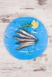 在蓝色厨房板的新鲜的沙丁鱼 免版税库存图片