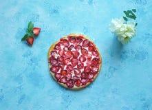 在蓝色厨房用桌上的草莓开放蛋糕 免版税图库摄影