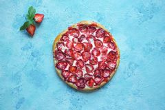 在蓝色厨房用桌上的草莓开放蛋糕 免版税库存图片