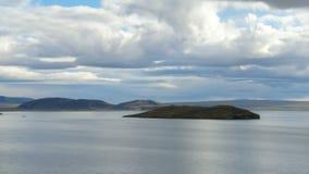 在蓝色口气的惊人的平静的风景,与湖、天空和低云,小海岛 股票录像