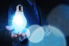在蓝色口气的电灯泡手中商人 库存图片