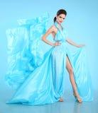 在蓝色吹的薄绸的礼服的时装模特儿 使Wo震惊的魅力 免版税图库摄影