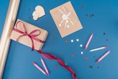 在蓝色和五彩纸屑隔绝的顶视图礼物盒、信封、蜡烛 免版税库存图片
