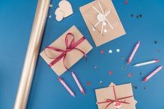在蓝色和包装纸隔绝的顶视图礼物盒、信封、蜡烛 库存图片