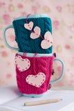 在蓝色和桃红色毛线衣的两个蓝色杯子有在笔记本的毛毡心脏的 免版税库存照片