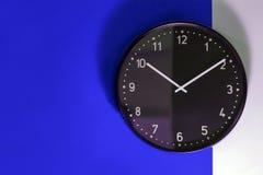 在蓝色和白色墙壁上的黑时钟 免版税库存图片