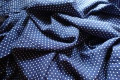 在蓝色和白色的起皱纹的织品与圆点印刷品 免版税库存图片