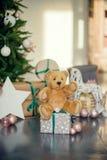 在蓝色和米黄颜色的新年装饰 戏弄熊、装饰白色灯笼和礼物盒在冷杉木下 球圣诞节查出的心情三白色 库存图片