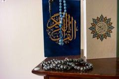 在蓝色和金子颜色的圣洁古兰经与阿拉伯祷告 库存图片