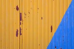 在蓝色和黄色绘的金属门 免版税库存图片