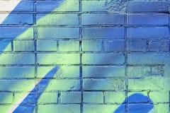 在蓝色和黄色颜色的几块被绘的砖在老肮脏的墙壁上,作为街道画 墙壁五颜六色的难看的东西纹理  免版税库存照片