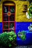 在蓝色和黄色墙壁的庭院窗口 免版税库存照片