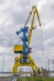 在蓝色和黄色的一台高口岸起重机以剧烈的天空为背景 图库摄影