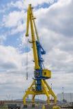 在蓝色和黄色的一台高口岸起重机以剧烈的天空为背景 免版税库存照片
