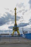 在蓝色和黄色的一台高口岸起重机以剧烈的天空为背景 免版税库存图片