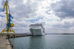 在蓝色和黄色的一台高口岸起重机以剧烈的天空和一艘大白色船为背景 免版税库存照片