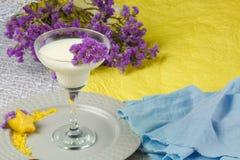 在蓝色和黄色背景的奶昔 与花的一个鸡尾酒 夏天饮料 食家的美丽的饮料 库存图片