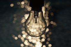 在蓝色和bokeh背景的电灯泡 库存图片