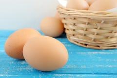 在蓝色困厄的木桌上的新鲜的鸡鸡蛋 免版税库存照片