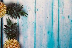 在蓝色土气木桌的成熟黄色菠萝 免版税库存照片