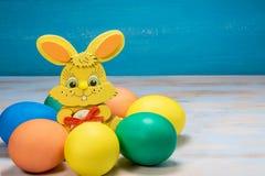 在蓝色土气木背景的复活节egge在圈子用颜色兔子 图库摄影