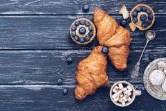 在蓝色土气木背景的新月形面包,蛋糕用蓝莓,蛋白甜饼 库存照片
