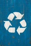 在蓝色土气老破裂的木盘区的白色回收的商标标志 免版税库存图片