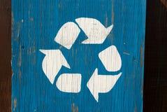 在蓝色土气老破裂的木盘区的白色回收的商标标志 库存图片