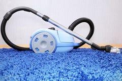 在蓝色地毯的吸尘器立场。 库存照片