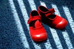 在蓝色地毯的红色鞋子 图库摄影