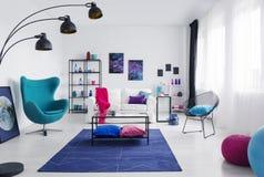 在蓝色地毯的表在现代客厅内部的扶手椅子旁边与海报和灯 实际照片 图库摄影