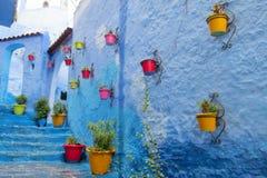 在蓝色城市墙壁和台阶的五颜六色的罐  图库摄影