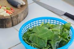 在蓝色塑料小箱和大蒜辣椒的无头甘蓝在木砍 图库摄影