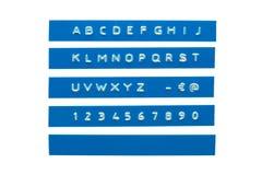 在蓝色塑料磁带上的压印的字母表 免版税库存图片