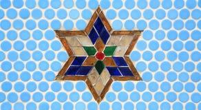 在蓝色墙壁上的五颜六色的玻璃星装饰 免版税库存图片