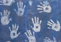 在蓝色墙壁上的白色油漆handprints 免版税库存照片