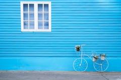 在蓝色墙壁上的白色窗口有自行车的塑造了花盆 库存图片