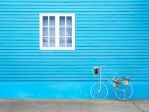 在蓝色墙壁上的白色窗口有自行车的塑造了花盆 免版税库存图片