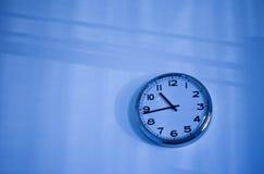 在蓝色墙壁上的蓝色时钟 免版税库存照片